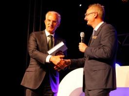 Metaalunie-voorzitter Fried Kaanen neemt het jubileumboek in ontvangst uit handen van Sales director Erik Spikmans van MCB