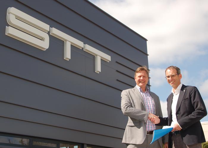Menno Kooistra (rechts) van STT Products en Martin van der Have van ABB Robotics schudden elkaar de hand bij het nieuwe pand van STT Products in Tolbert, dat op 20 mei feestelijk wordt geopend.