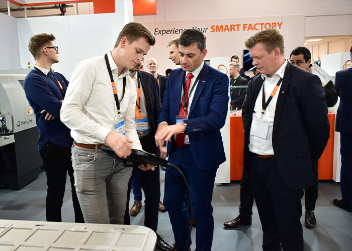 Douwe Corel van Dymato Automation demonstreert de werking van de HCR-12 cobot in combinatie met de HCT-1200 tafel aan andere Europese Hanwha Robotics distributeurs.