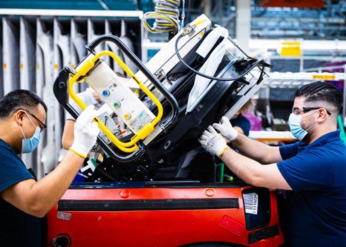 Medewerkers van VDL Nedcar die aan de assemblagelijn dicht bij elkaar werken, zijn onder meer uitgerust met persoonlijke beschermingsmiddelen, zoals mondkapjes, veiligheidsbrillen en handschoenen. (Foto: VDL)