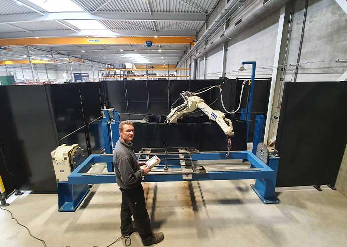"""Marvin van de Mortel programmeert de lasrobot met de hand aan de machine. Offline programmeren is een stap die hij eenvoudig kan maken bij verdere groei van zijn bedrijf. """"Robotlassen is de toekomst."""""""