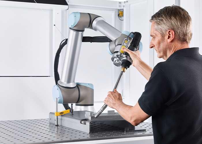 De bediener kan de cobot met de hand over het werkstuk bewegen. Geïntegreerde sensortechniek zorgt ervoor dat hij zich eenvoudig laat leiden.