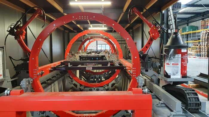 In de cabine staat een grote carrousel met aan weerzijden rails waarop twee lasrobots over de hele lengte van de cel kunnen bewegen.