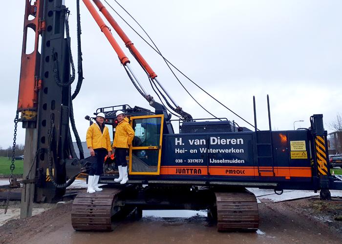 Commercieel directeur Harry Werkman (links op de rupsband) en technisch directeur Henry Heidema bij het slaan van de eerste paal van de nieuwbouw van DICTATOR.