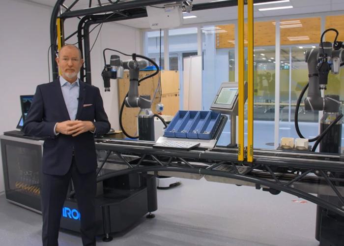 Tim Foreman laat tijdens een online Technology Update van het Fieldlab Flexible Manufacturing de Omron New Technology (ONT) opstelling zien. Deze zelflerende assemblagelijn verbetert mens-machine interactie