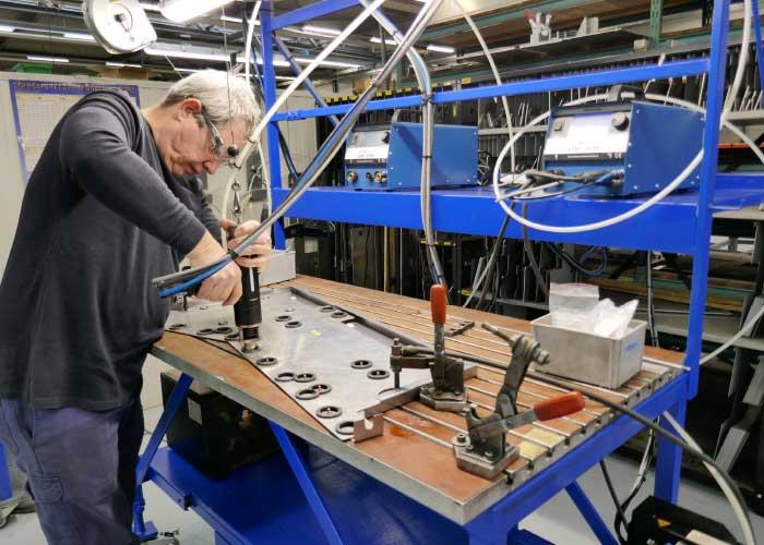 Lascoördinator Jan Gielens demonstreert het stiftlassen. De twee stiftlasmachines bevinden zich op ooghoogte. Hierdoor kan de persoon die het stiftlaspistool bedient alle informatie van het display aflezen terwijl hij last.