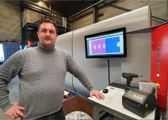 """Commercieel manager Cor de Groot bij het beeldscherm dat het uitsorteren van snijdelen makkelijk maakt en het apparaat dat gelijk de stickers print. """"Het snijwerk is nu geautomatiseerd. Alle producten die uit laser komen zijn getraceerd."""""""