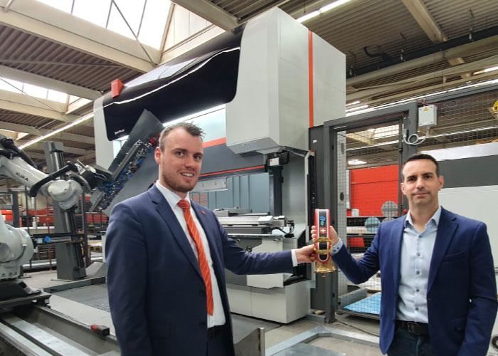 Joris Meesters (links) van Bystronic Benelux overhandigt de traditionele Zwitserse koebel aan COO Dennis Geerings van Wilvo voor de investering in de buigcel.