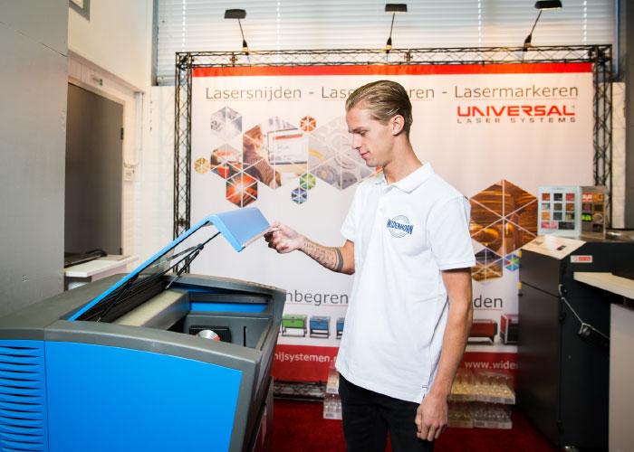 Dinant Heezen, de vijfde generatie binnen familiebedrijf Widenhorn, demonstreert een lasersysteem van Universal Laser Systems.